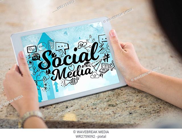 Hands holding tablet showing black social media doodles against sky