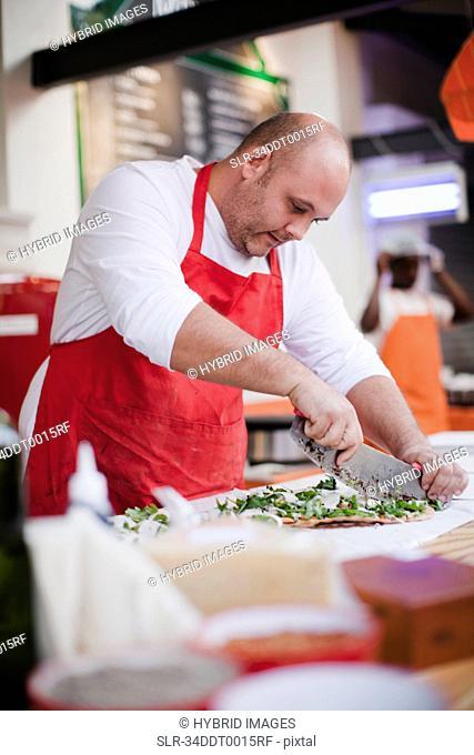 Chef slicing pizza in kitchen