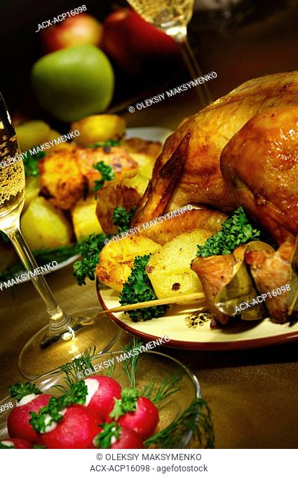 Artistic light-painted festive food still life in golden colors with a roast chicken fried appetizing potatoes and two glasses of champagne