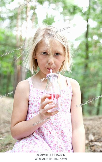 Girl drinking from glass of infused water in forest