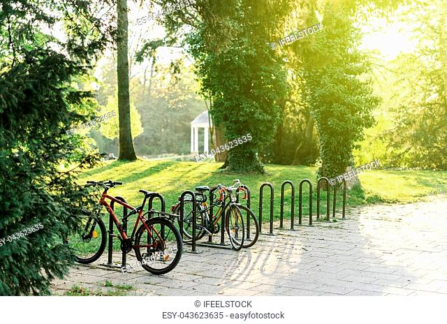 Bicycle parking in French park of Orangerie in Strasbourg on a warm summer day with sun flare, sunlight