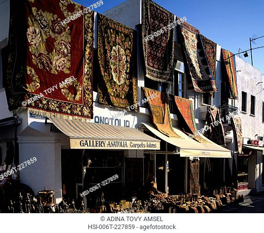 Morocco. Marrakech. Carpets displayed on walls outside shop