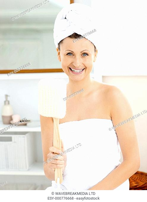 Charming young woman with a towel holding a brush in the bathroom at home