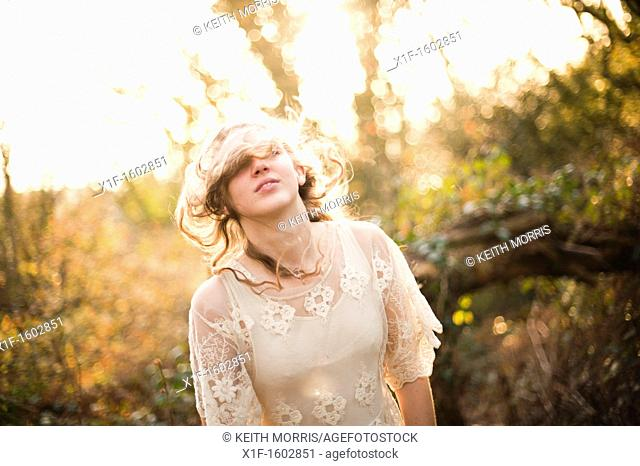 a slim blonde woman girl alone in woodland autumn afternoon daytime UK