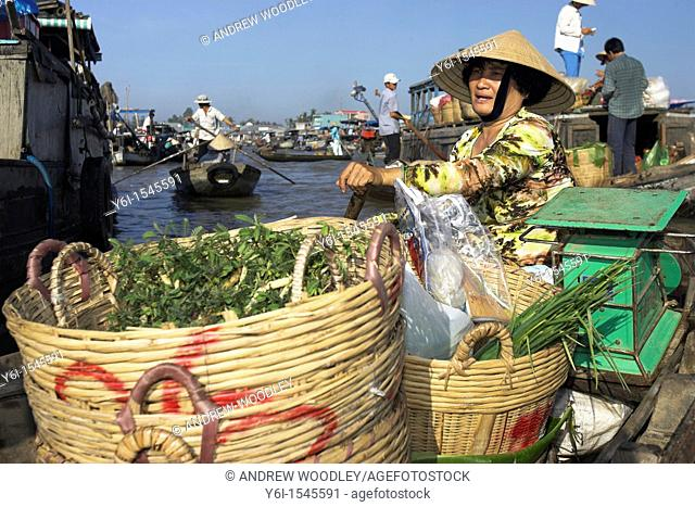 Woman in conical hat with baskets of vegetables paddles her boat at Cai Ran floating market near Can Tho Vietnam