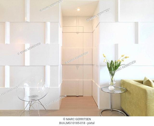 Modern interior with door camouflaged with wall