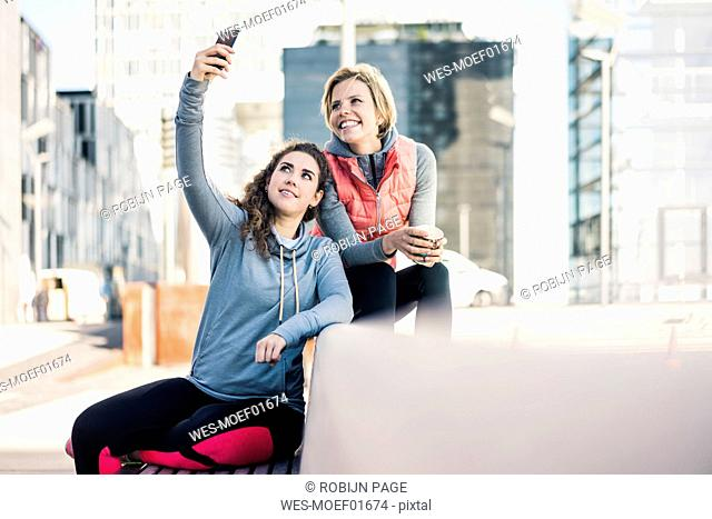Girlfriends taking a break after training, using smartphone