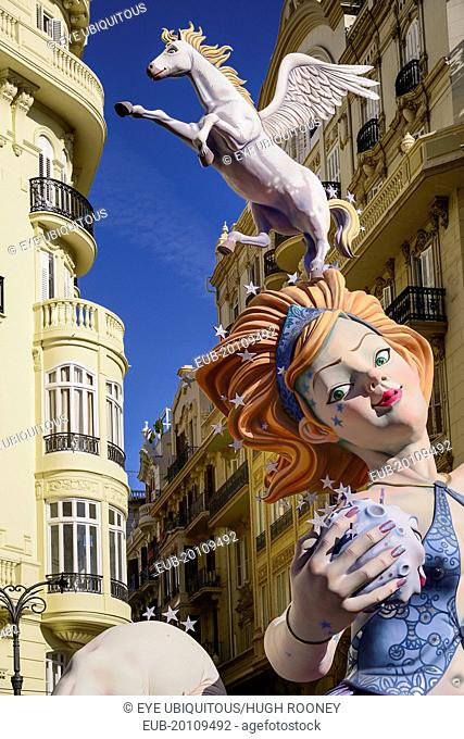 Female Papier Mache figure with a horse on her head in the street during Las Fallas festival