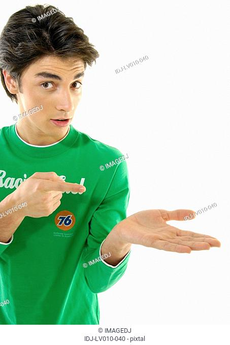 Portrait of a young man pointing towards his palm