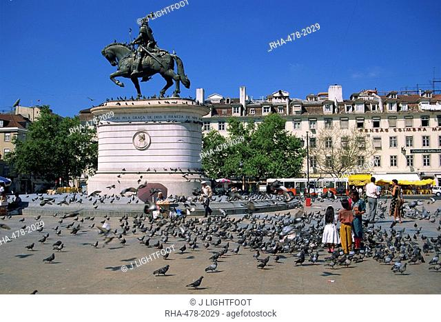 Children feed pigeons in Figueira Square in Lisbon, Portugal, Europe