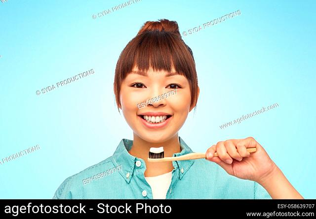 asian woman with toothpaste on wooden toothbrush