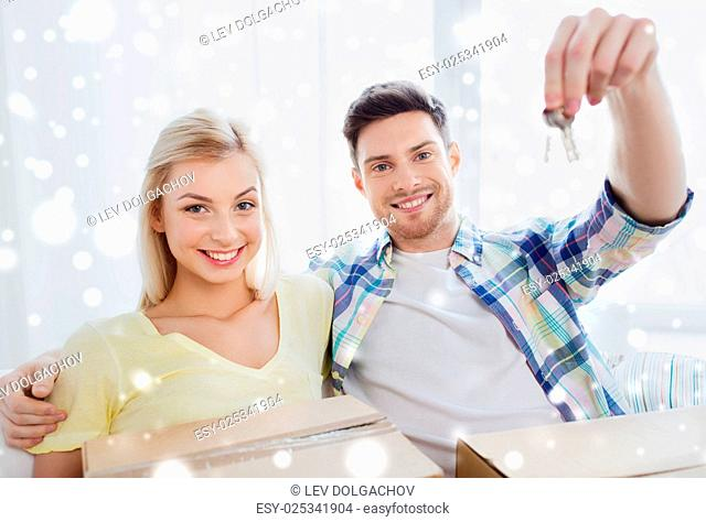 people and real estate concept - happy couple with key and boxes moving to new home over snow