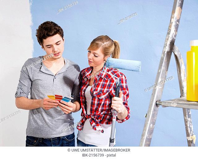Young couple using colour cards to select a wall paint colour