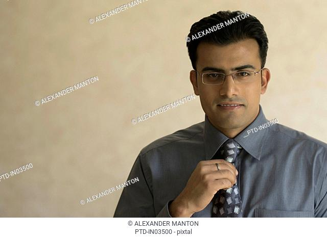 India, Portrait of young businessman adjusting his tie