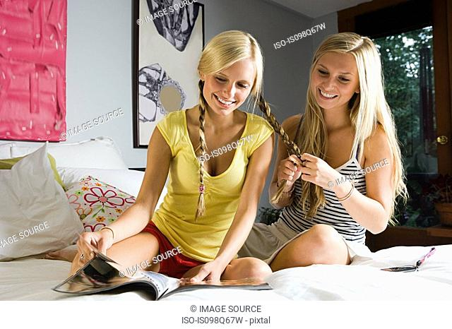 Girl plaiting sisters hair