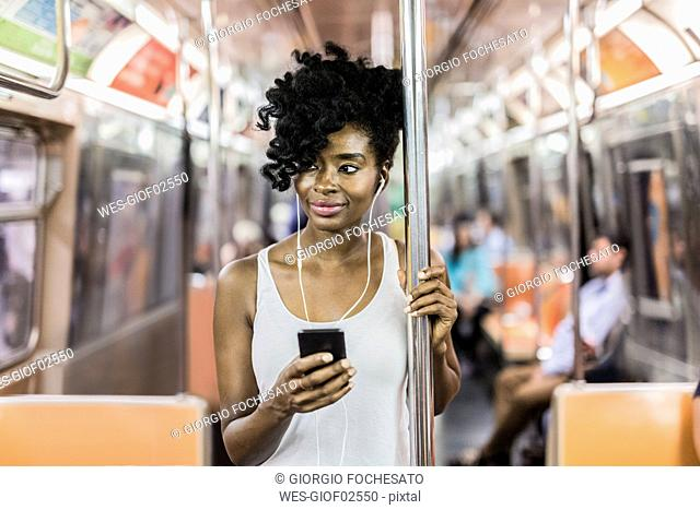 USA, New York City, Manhattan, portrait of relaxed woman with cell phone in underground train