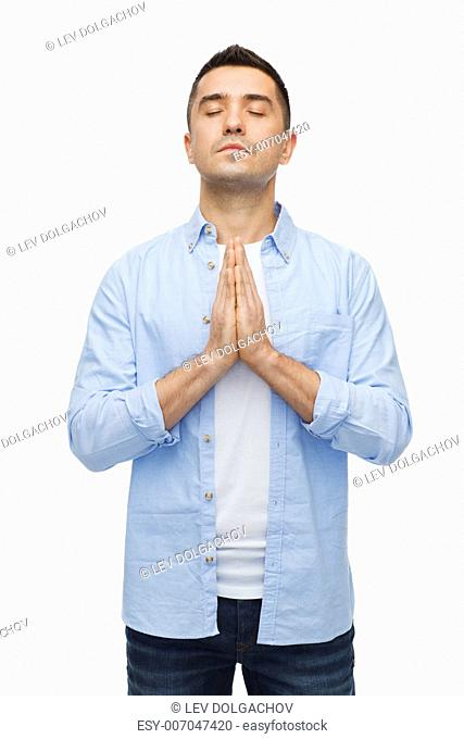faith in god, religion and people concept - happy man with closed eyes praying