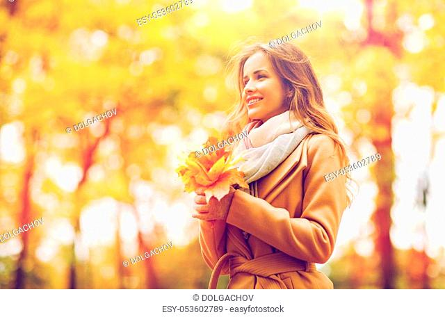 season and people concept - beautiful young woman with maple leaves walking in autumn park