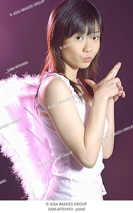 Young woman wearing angel wings, looking at camera