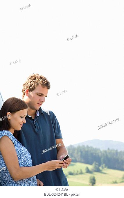 young couple reading message on mobile phone