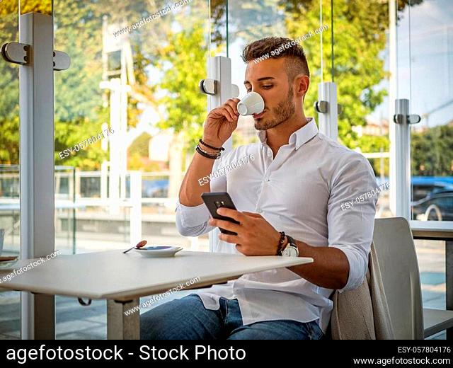 Close up of Handsome Young Man Drinking Coffee at the Shop While Looking at Cell Phone