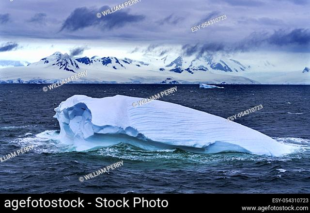 Floating Blue Iceberg Glaciers Snow Mountains Sea Water Charlotte Bay Antarctic Peninsula Antarctica. Glacier ice blue because air squeezed out of snow
