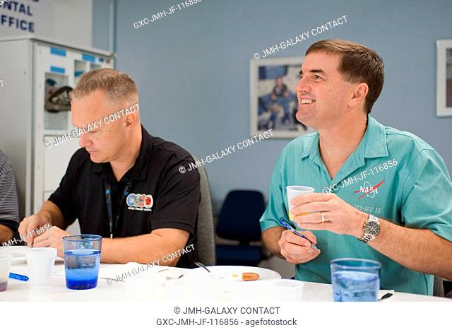 NASA astronauts Doug Hurley (left), STS-135 pilot; and Rex Walheim, mission specialist, participate in a food tasting session in the Habitability and...