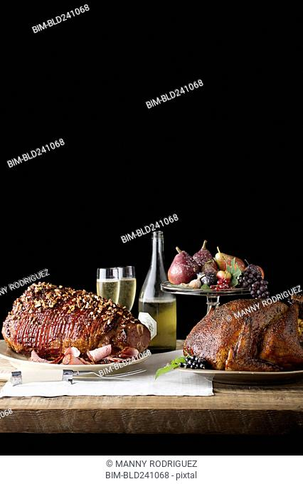 Champagne, fruit and meat on wooden table