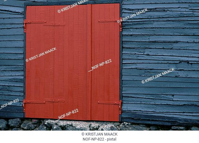 Bright red wooden door on the side of grey wooden structure