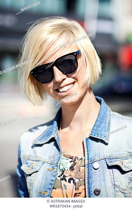 Happy young woman wearing sunglasses in city on sunny day