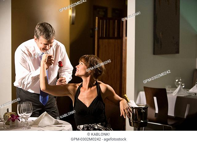 Mature man with red rose kissing the hand of sexy woman in restaurant