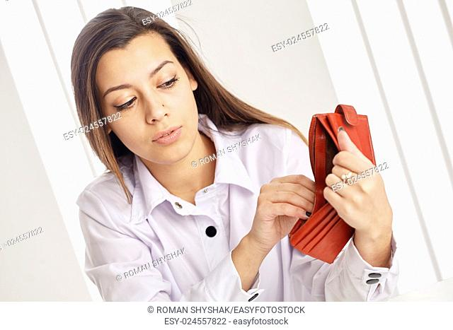 Young attractive woman searching money in the wallet