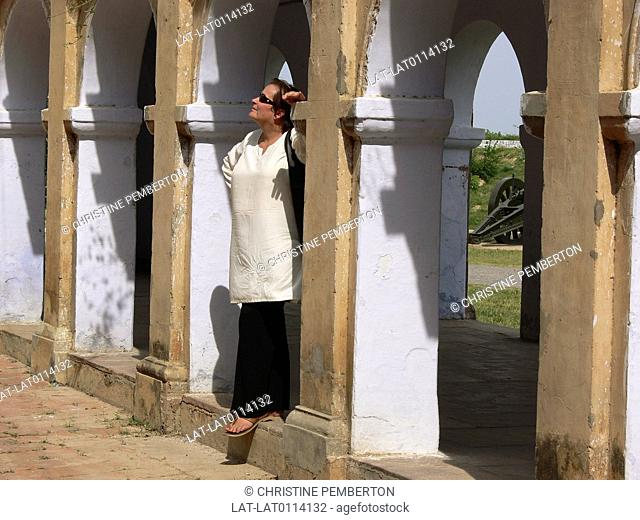 La Martiniere Boys' College,founded in 1836. Gothic arches in courtyard. View of cannon. Woman standing in shade. Wearing sunglasses