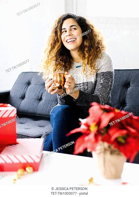 Happy woman on sofa, holding mug with Christmas gifts in foreground