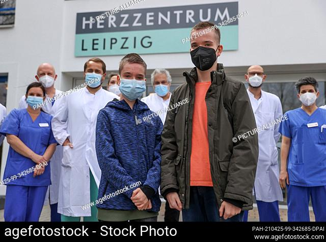 22 April 2021, Saxony, Leipzig: Twins Jamie (l) and Kilian and the paediatric heart surgery team stand in front of the Heart Centre Leipzig