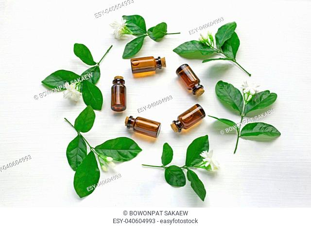 Dark brown Bottles of essential oil with jasmine flower and leaves on white background