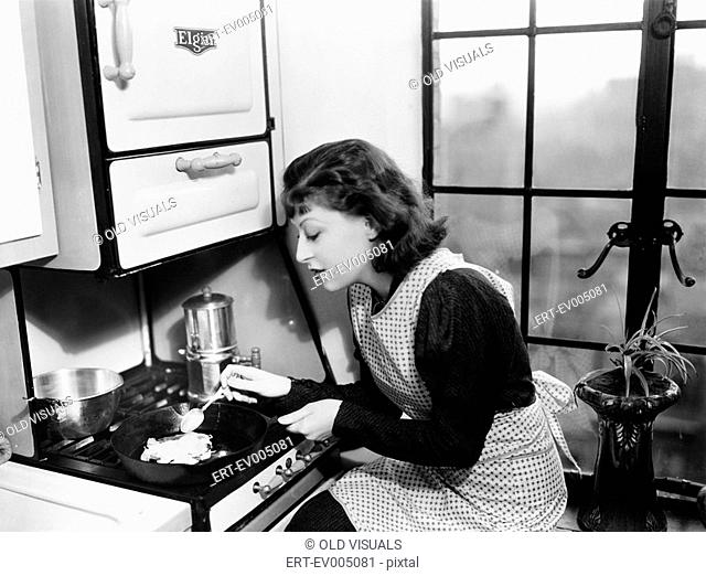 Woman in her kitchen preparing food on the stove All persons depicted are not longer living and no estate exists Supplier warranties that there will be no model...