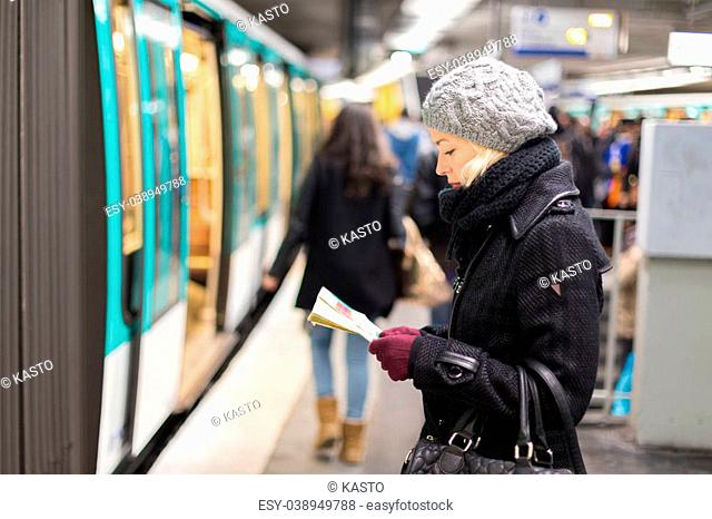 Casually dressed woman wearing winter coat, waiting on a platform for a train to arrive, orientating herself with public transport map