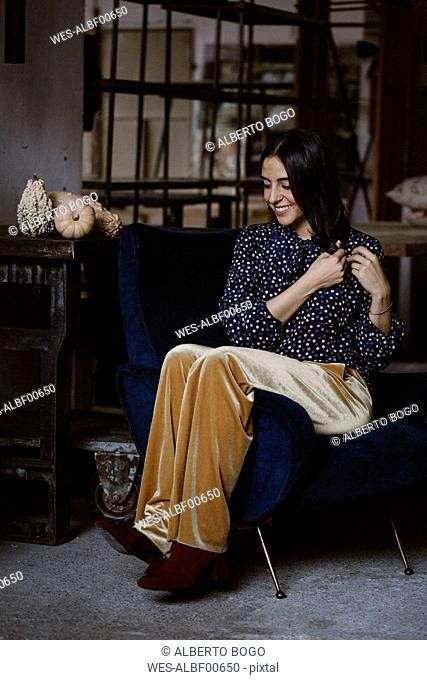 Smiling young woman sitting on armchair in a loft