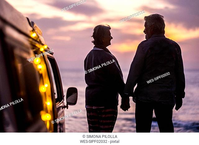 Senior couple traveling in a vintage van, watching sunset at the sea