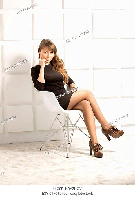 Young woman sitting on white chair at studio against bricked wal