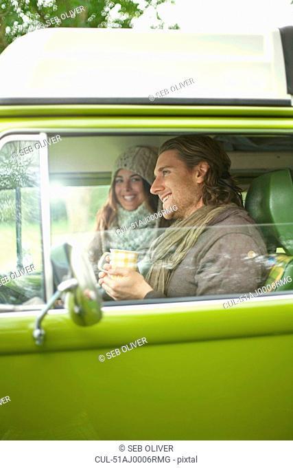 Smiling couple drinking coffee in van