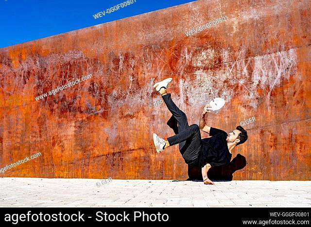 Young man holding face mask while dancing on footpath during sunny day
