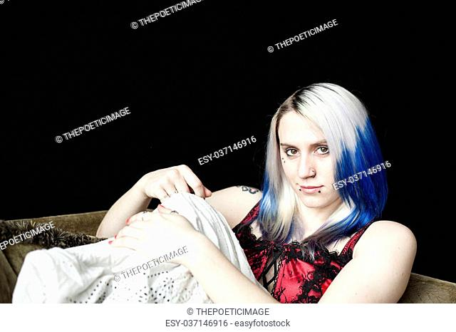 Portrait of a beautiful young woman with blue hair shot and red corset on a black background
