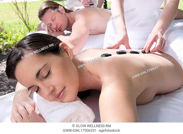 Couple receiving hot stone therapy from massage therapists