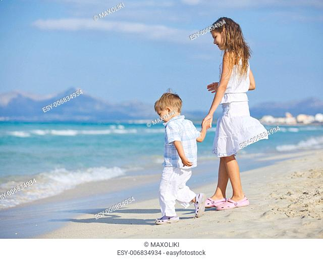 Young beautiful girl and boy playing happily at pretty beach. Majorca