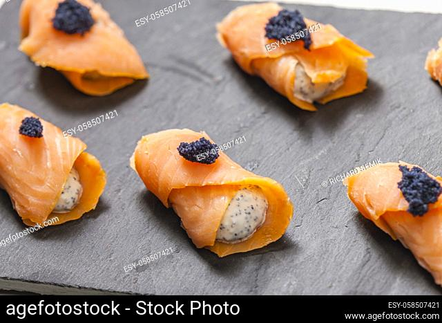 smoked salmon rolls filled with cream cheese and black caviar