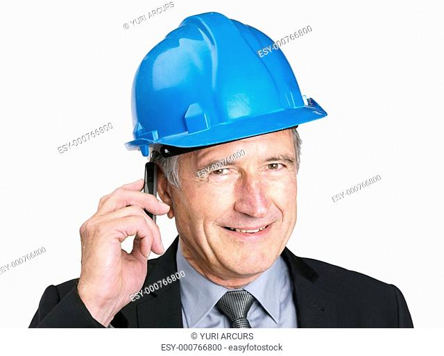Closeup portrait of a handsome senior male construction worker speaking on mobile phone - Copyspace