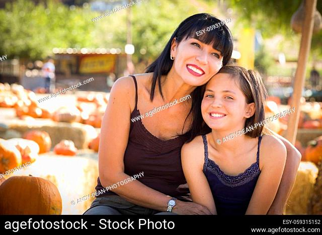Attractive Mother and Baby Daughter Portrait in a Rustic Ranch Setting at the Pumpkin Patch.
