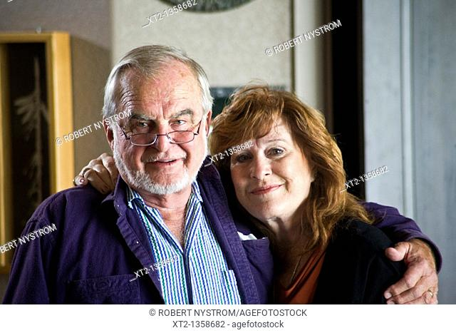 A mature older couple hugging each other smiling at the camera